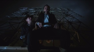 The Fearsome Dr. Crane- Gerald Crane, played by Julian Sands, dangles Adam Jodowsky, played by Jim Ford, over a rooftop