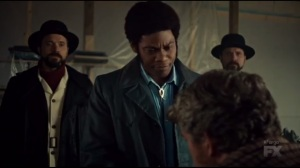 Before the Law- Mike Milligan, played by Bokeem Woodbine, types a letter while also choking Skip