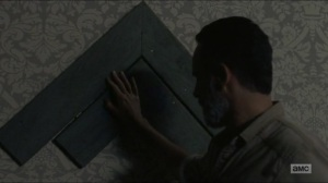 Warning Signs- Rick rests his hand on Carl and Judith's handprints- AMC, The Walking Dead