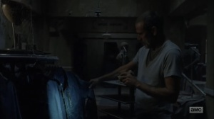 Adaptation- Negan examines a leather jacket at a men's clothing store- AMC, The Walking Dead