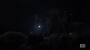 Squeeze- About to jump across rocks- The Walking Dead, AMC